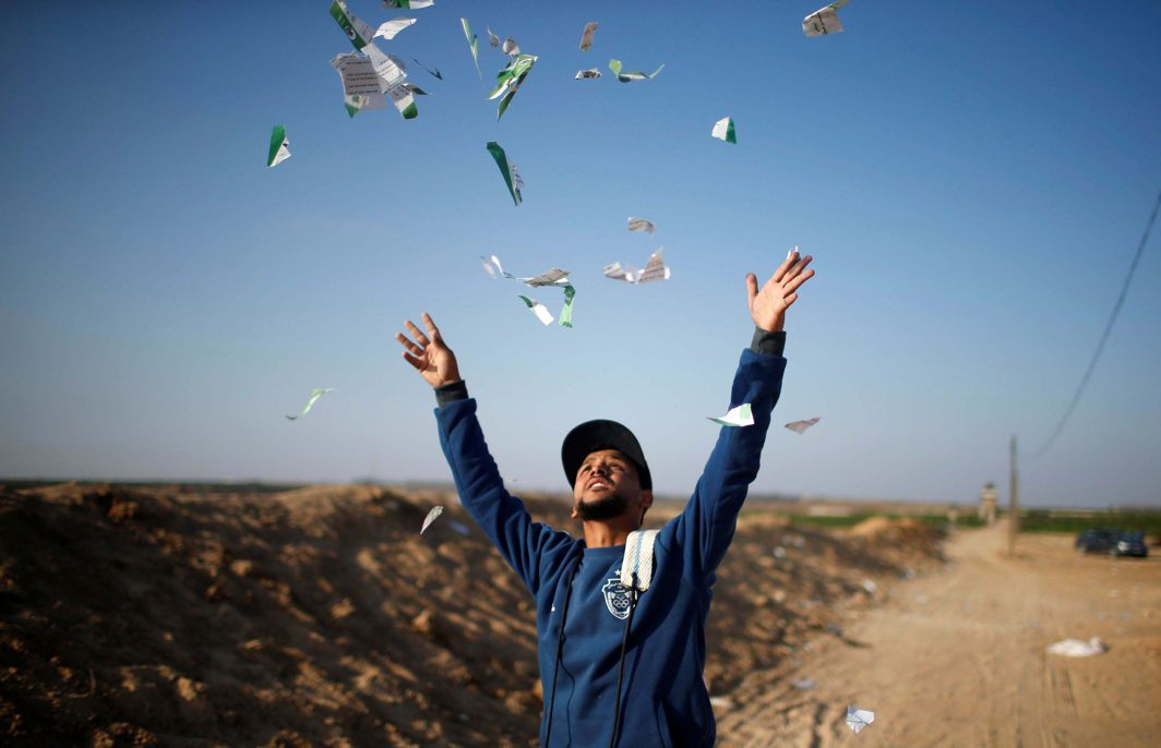 A Palestinian man throws leaflets dropped by the Israeli military during a protest against the U.S. embassy move to Jerusalem and ahead of the 70th anniversary of Nakba, at the Israel-Gaza border, east of Gaza City, Reuters/UNI