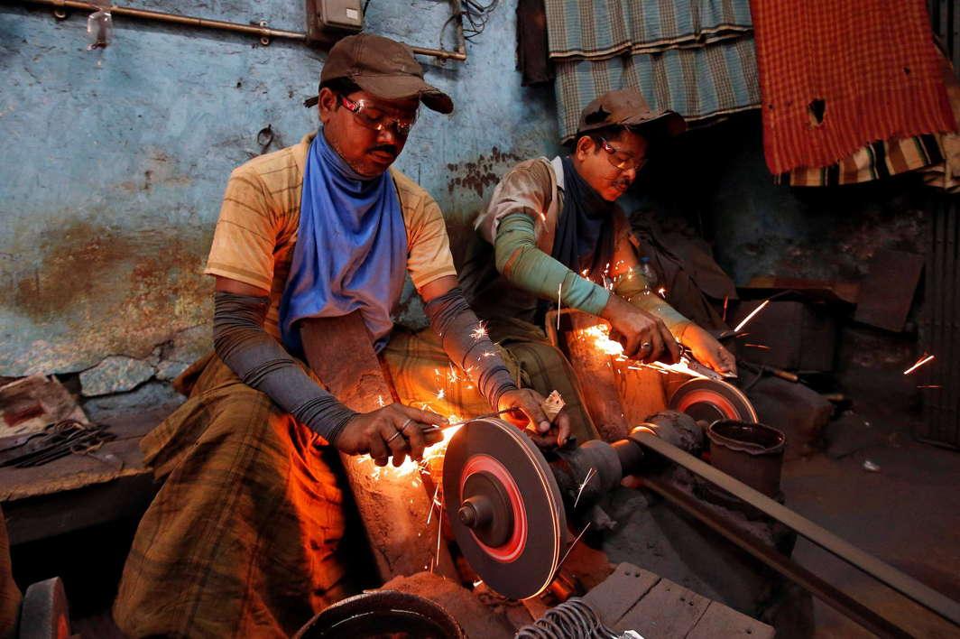 Workers sharpen scissors inside a workshop in Kolkata, India, Reuters/UNI