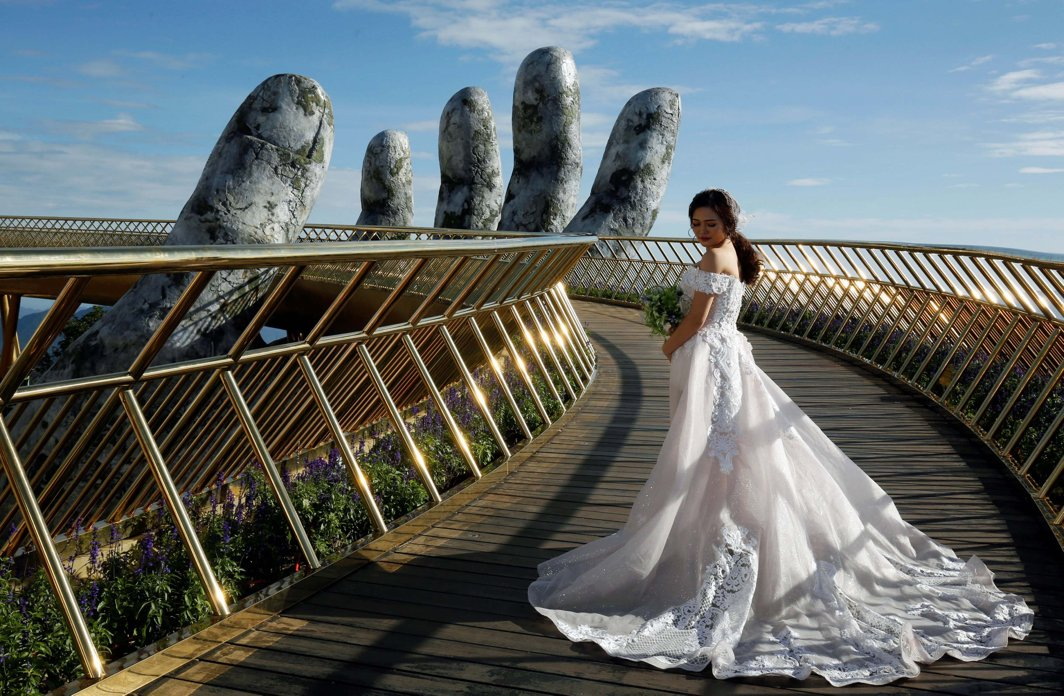 A Vietnamese bride poses for her wedding photos on Gold Bridge on Ba Na hill near Danang city, Vietnam, Reuters/UNI
